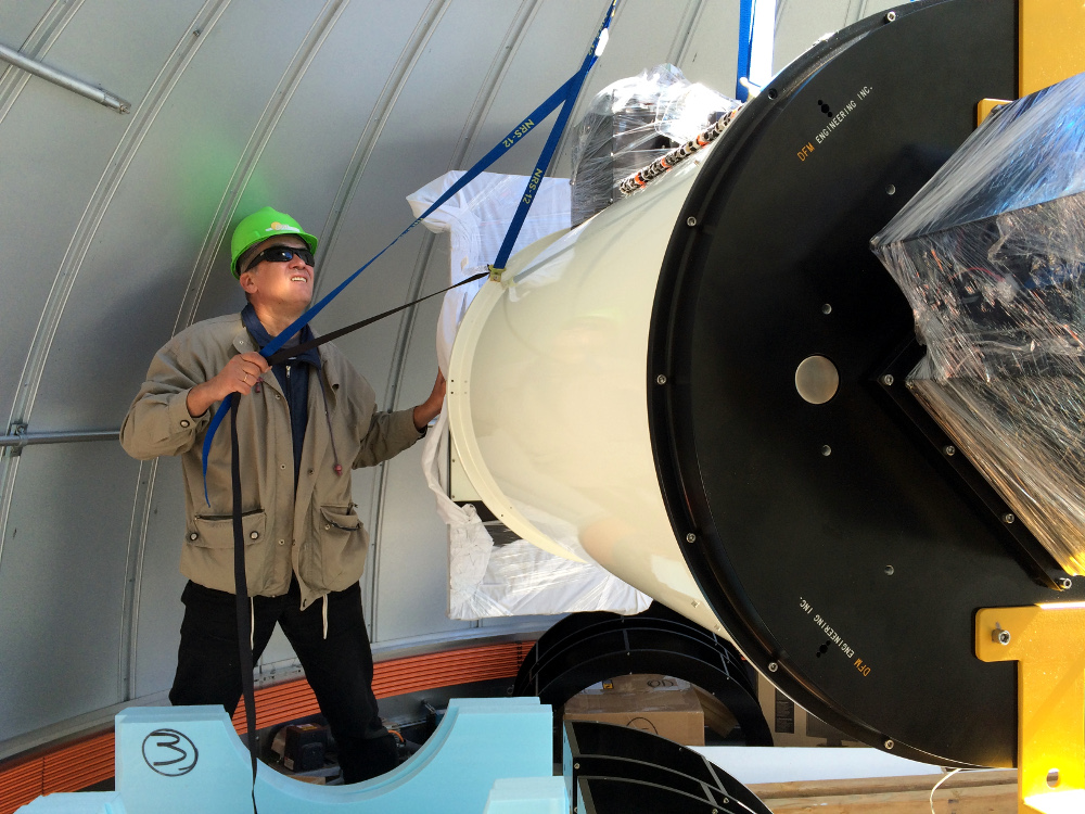 Andrei assists as the the new telescope is lowered into the observatory with a crane.